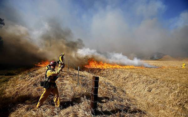 Firefighters set backfires on Federal Indian Reservation land near Banning, where a wildfire burned more than 1,500 acres and destroyed several homes on Wednesday afternoon.