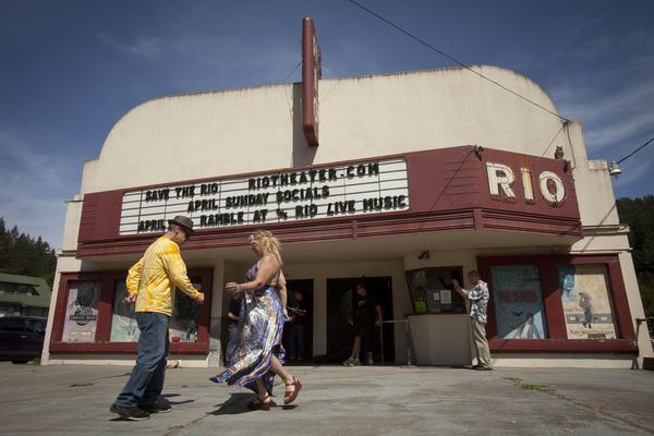 Robert Neir and Sage O'Connell dance to bluegrass music outside the Rio Theater as musicians practice before a fundraising concert.