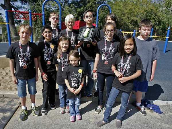 The 2% Milk robotics team pose for a group photo after they showed the entire school how their robot picks up and deposits tennis balls at Palm Crest Elementary School in La Canada Flintridge on Friday, April 26, 2013.