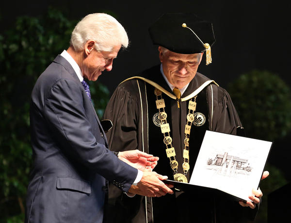 Former president Bill Clinton receives on honory doctorate degree from University of Central Florida president Dr. John Hitt during the commencement ceremony for the College of Health and Public Affairs and the College of Medicine's Burnett School of Biomedical Science, at UCF in Orlando, Fla., Thursday, May 2, 2013