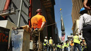 New York showed its colors on Thursday as flag-draped pieces of the silver spire, designed to be the crown of the reconstructed World Trade Center, were hoisted into the sky.
