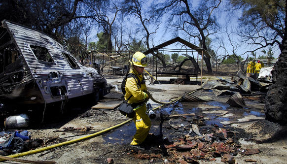 A firefighter pulls his hose through debris in the backyard of a burned home and destroyed motor home after strong winds fueled a vegetation fire in Jurupa.