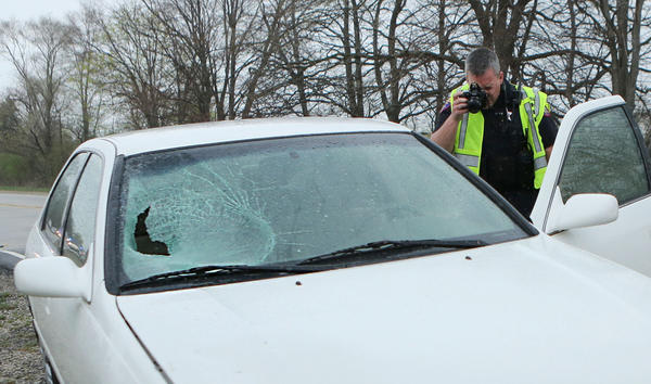 A Lake County Sheriff's Police Officer photographs car involved in a fatal bicycle accident on Route 45 north of Grand Avenue in rural Lake County, Ill. on May 2, 2013.