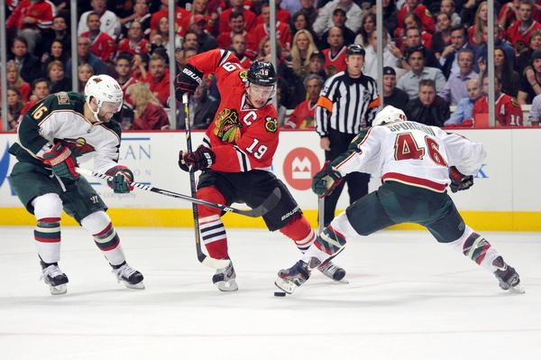 Jonathan Toews moves the puck past the Wild's Jared Spurgeon and Jason Zucker during the third period.