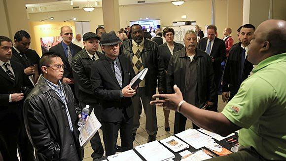 BNSF Railway manager military staffing John Wesley, right, talks with job applicants at the Recruit Military Chicago Veteran Job Fair at Macy's on State Street in Chicago April 25.