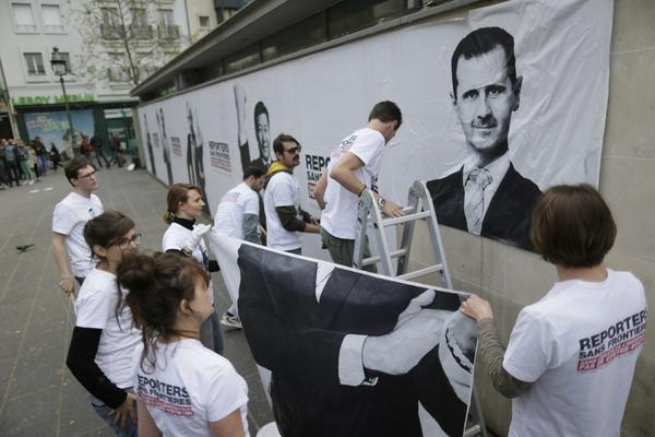 Activists from Reporters Without Borders hang a poster of Syrian President Bashar Assad in Paris to mark World Press Freedom Day.