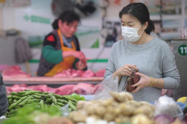 A woman wears a mask as she shops in a market in Shanghai in April. Bird flu has Chinese shoppers fearful of poultry. Now a three-month national campaign has found rat and other uninspected meats disguised as beef and mutton.