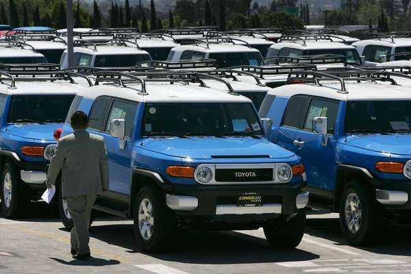 A salesman walks past rows of Toyota FJ Cruiser SUVs at a dealership in California. Toyota is issuing another recall of the vehicles, this time for 11,489 that have a headlamp problem that could blind oncoming drivers.