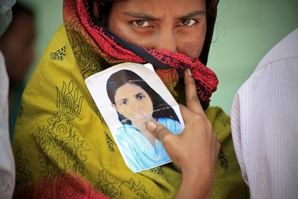A woman holds a photo of her missing sister on Friday, nine days after a building collapsed in Savar, Bangladesh.