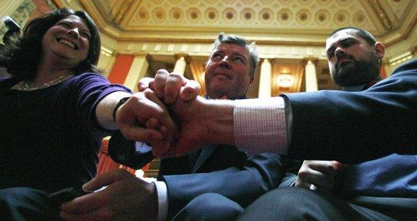 Leaders of Rhode Islanders United for Marriage clasp hands after vote to pass a gay marriage bill at the State House in Providence on Thursday.