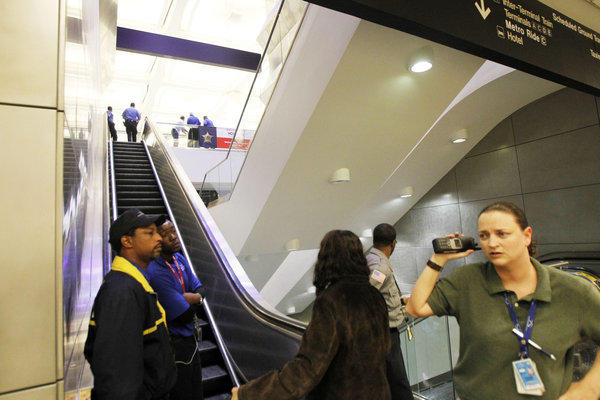 Security officials at Bush Intercontinental Airport stand at the bottom of the escalators as police investigate a shooting near Terminal B on Thursday in Houston. Authorities say a man from Beaumont, Texas, shot himself in the head.