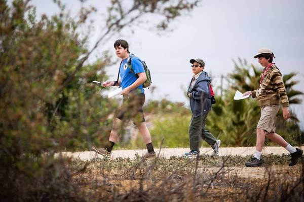 Jon Engstrom, 16, left, Luke Tomaneng, 11, and Jack Cotter look for a check point during an orienteering competition at Lake Balboa in Balboa Park in Encino.