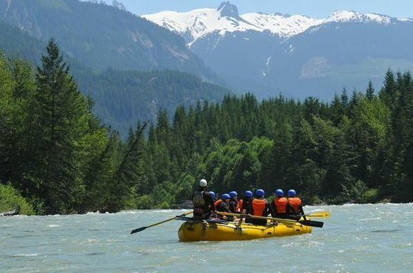 River rafters paddle their way through spectacular scenery along the Elaho River in British Columbia.
