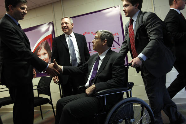 U.S. Rep. Brad Schneider, from left, of the 10th District, and U.S. Sen. Dick Durbin meet U.S. Sen. Mark Kirk, center, as Kirk arrives at LEARN Public Charter School in North Chicago, following a visit to adjacent Naval Station Great Lakes. At right, Kirk staffer Andrew Weissert pushes the wheelchair used by Sen. Kirk.