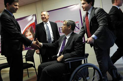 U.S. Rep. Brad Schneider, from left, 10th District, and U.S. Sen. Dick Durbin meet U.S. Sen. Mark Kirk, center, as Kirk arrives at LEARN Public Charter School in North Chicago, following a visit to adjacent Naval Station Great Lakes. At right, Kirk staffer Andrew Weissert pushes the wheelchair used by Sen. Kirk.