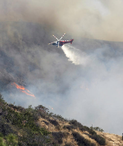 A helicopter makes a water drop on a brush fire in the Chevy Chase Canyon area of Glendale on Friday, May 3, 2013.