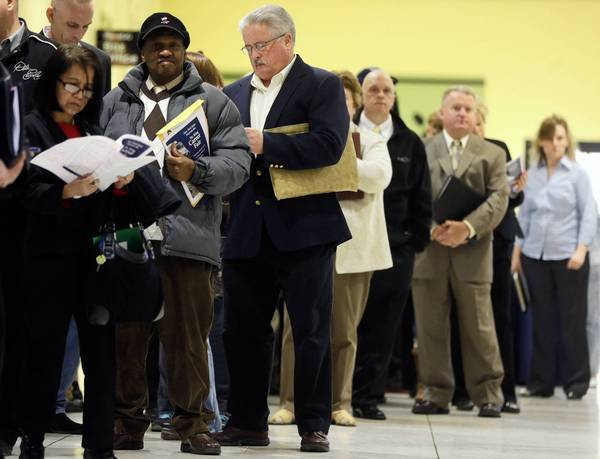The Labor Department reported Friday that 165,000 net new jobs were added last month and sharply upgraded the totals for February and March by a combined 114,000 positions. Above, job seekers attend a career fair in April at the Empire State Plaza Convention Center in Albany, N.Y.