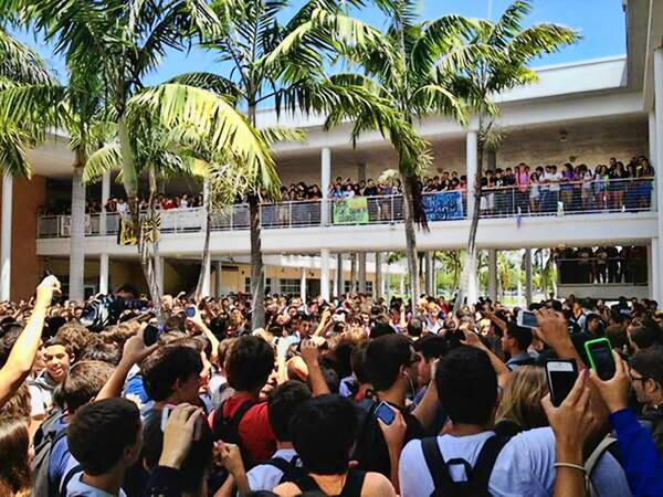 Students gather at Cypress Bay High School as a fight breaks on in the Quad area Friday.