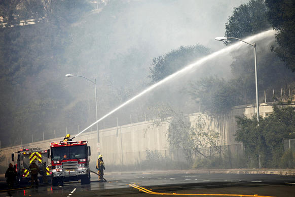Firefighters on Harvey Drive hose down brush along the Glendale Freeway as a fire burns in the area.