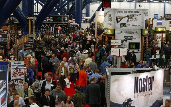 Gun enthusiasts attend the National Rifle Assn. annual convention in Houston. A fatal shooting at the Houston airport was a frequent topic of discussion at the convention.
