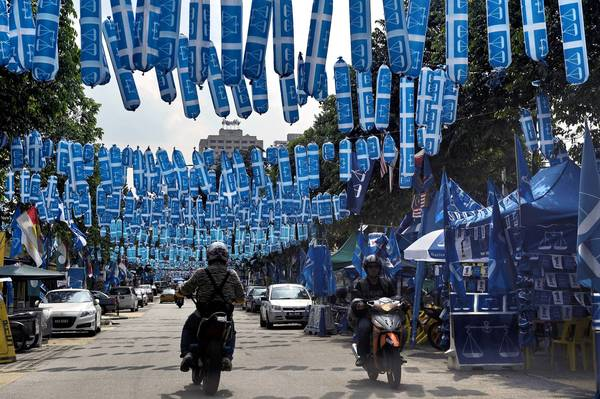 Hundreds of balloons bearing the logo of the ruling coalition hang over a street in Kuala Lumpur, Malaysia.