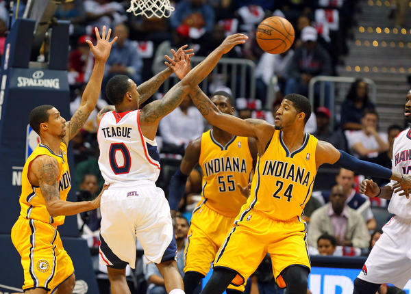 The Hawks' Jeff Teague passes off under pressure from Pacers defenders George Hill, Roy Hibbert and Paul George in the first half.