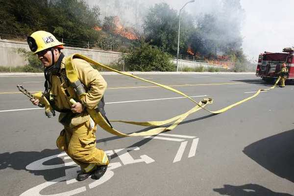 A fireman from Glendale Station 25 runs with hose to connect to a hydrant on Harvey Avenue to battle a brush fire that erupted along the road which was part of a bigger fire in the Glenoaks and Chevy Chase canyons in Glendale on Friday, May 3, 2013. Hundreds of homes were evacuated.