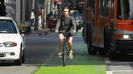 The reason the bike lane on Spring Street in downtown Los Angeles is bright fluorescent green is so drivers and bicyclists alike can see it easily and avoid running into one another. However, the very conspicuousness of that color has brought on a collision between politics and business in the city.