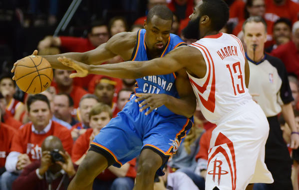 The Thunder's Serge Ibaka tries to drive against the Rockets' James Harden.