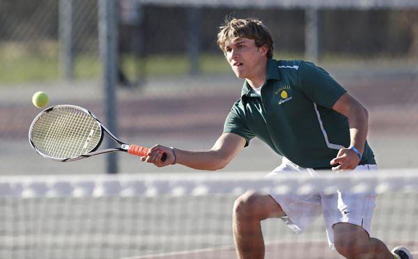 Aberdeen Roncalli's Kyle Martin reaches to return a volley at the net during a doubles match against Aberdeen Central Friday at the Northern State University tennis courts.
