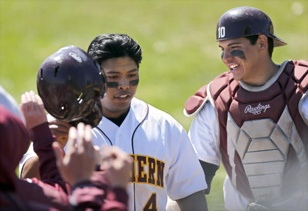 Northern State University's Robbie Rocamora, center, is greeted by teammates, including Buddy Traxler, right, after Rocamora hit a solo home run during Friday's second game against the University of Minnesota-Duluth at Fossum Field.