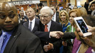 Berkshire Hathaway CEO Warren Buffett (C) shakes hands with a shareholder just before the company's annual meeting in Omaha
