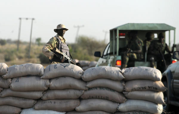 An officer of the Joint Military Task Force (JTF) stands beside sand bags at a road block in the northeastern Nigerian town of Maiduguri.