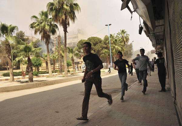 People run for cover after what activists said was shelling by forces loyal to Syria's President Bashar al-Assad in Raqqa province, eastern Syria.