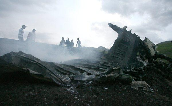 Locals watch the smoldering wreckage at the site of the U.S. KC-135 tanker aircraft crash near Chaldovar, Kyrgyzstan on Friday.