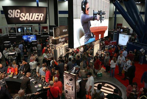 Visitors to the National Rifle Assn. convention in Houston crowd the booth of Sig Sauer, a maker of handguns and rifles.