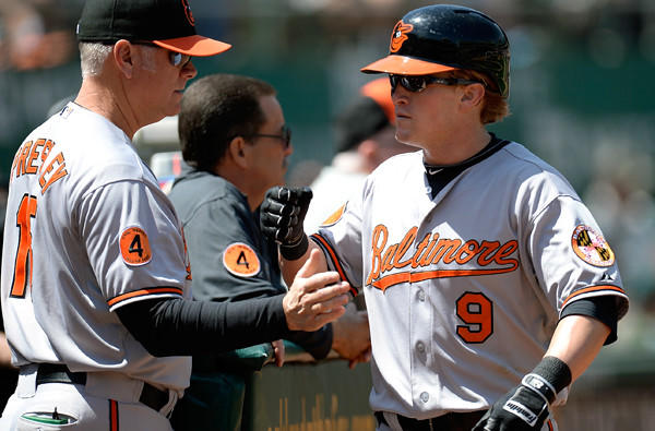 Orioles outfielder Nate McLouth is congratulated by hitting coach Jim Presley scoring a run against the Athletics during a game last week in Oakland.