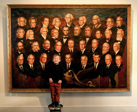 "Presidential enthusiast Arden Hayes, 5, poses in front of a painting titled ""A Presidential Pantheon,"" by Victor Lee, at the Nixon library in Yorba Linda."