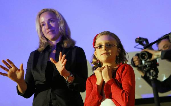 Documentary photographer Lisa Kristine, left, introduces Vivienne Harr, 9, during a lecture at the Orlando Museum of Art on Saturday, May 4, 2012.