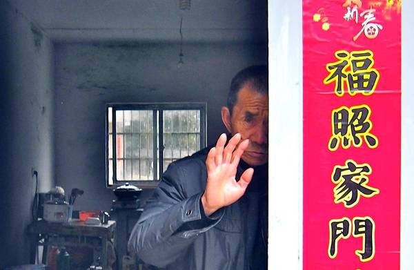 Qiu Riren, facing a prison sentence for the murder of a doctor during the Cultural Revolution, stands in the doorway of his home, waving off visitors. 3/28/2013.