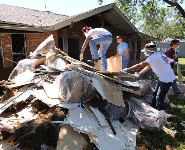 Students clean debris at a home in West, Texas, that was damaged in the fertilizer plant explosion that killed 14 people last month. Lawyers said Saturday the plant only had $1 million in liability coverage.