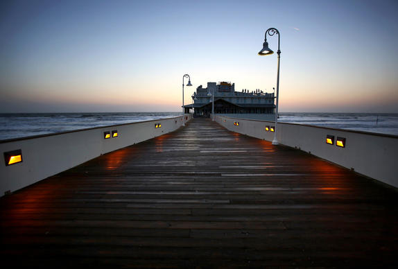 The sun starts to rise over the Daytona Beach Pier, or Main Street Pier as it's called, in Daytona Beach on April 23, 2013.