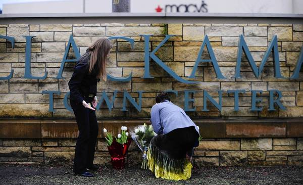 Mourners put flowers at the entrance to the Clackamas Town Center mall outside Portland, Ore., the day after Jacob Roberts fatally shot two people and then himself. Roberts, 22, had no history of violence. His friends knew him as a joker.
