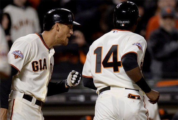 San Francisco Giants' Hunter Pence congratulates Francisco Peguero (14) after Peguero scored the game-tying run on a sacrifice fly off the bat of Pablo Sandoval in the seventh inning.
