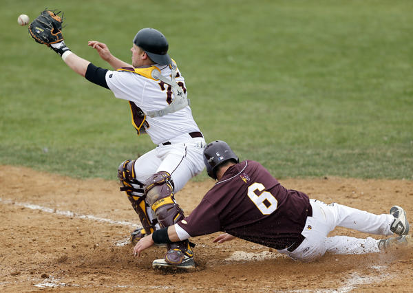 Northern State University's Clayton Nutting slides in behind University of Minnesota-Duluth's Tommy Bodeker, left, to score in the bottom of the sixth inning of Saturday's first game at Fossum Field. The run proved to be the game winner as the Wolves hung on for a 5-4 victory. photo by john davis taken 5/4/2013