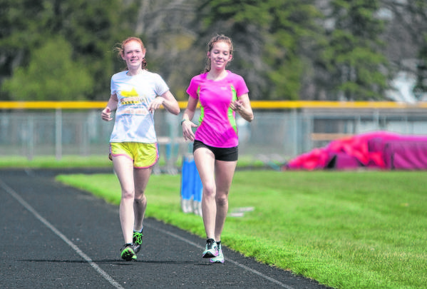 Adams High School students Aubrey Curl, left, and Michaela Lewis jog around the track at Adams High School on Monday to warm up for track practice. The two runners are organizing a 5K race next month for Hannah & Friends.