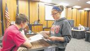 Adams High School Mock Trial attorney Becca Neal shows documents to witness Cody Hoban during questioning in a practice trial inside a courtroom in the St. Joseph County Courthouse in South Bend.