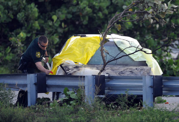 A Broward Sheriff's deputy places a tarp on a sedan to cover a man who was fatally shot Sunday in Oakland Park on southbound I-95 just south of Commercial Boulevard. I-95 was closed for several hours because of the incident.