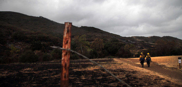 With the Springs fire in Ventura County reported 60% contained as of Sunday morning, firefighters walk through a burned-out area of Newbury Park.