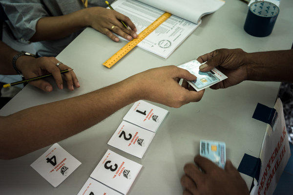 Election officials examine voter identification cards at a polling station in Kuala Lumpur, Malaysia, on Sunday. The governing National Front coalition won a narrow victory, but some opposition supporters said there was evidence of vote fraud.